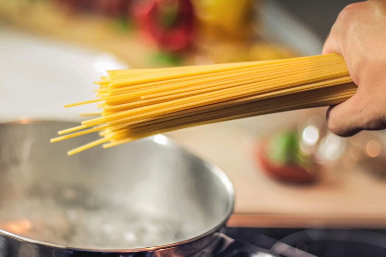 cuire des pâtes : des spaghettis au-dessus de l'eau bouillante