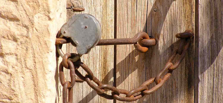 Vieille porte en bois fermée par une chaine rouillée et un cadenas